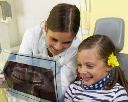 Young Dentist showing a girl an x-ray of her teeth | Preventative Orthodontics for Kids | Alluring Smiles in Mesa, AZ - Dr. Javier Portocarrero