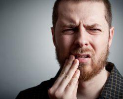 Man suffering from dental pain | TMJ Treatment | Alluring Smiles in Mesa, AZ - Dr. Javier Portocarrero